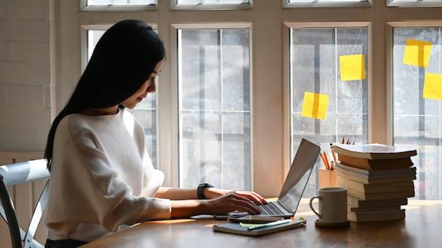 Mujer joven escribiendo en la computadora portátil.