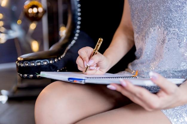 La mujer joven está escribiendo notas y planeando su horario, metas, logros y planes futuros. mujer con manicura festiva con pluma escribiendo en el cuaderno, tomando notas en su diario.