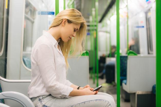 Mujer joven escribiendo en un teléfono inteligente en el tren del metro de londres