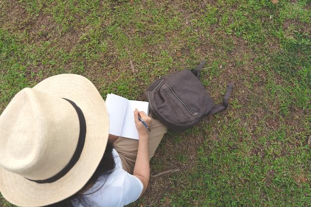Mujer joven en la escritura del sombrero en el cuaderno con el lápiz en hierba en parque al aire libre.