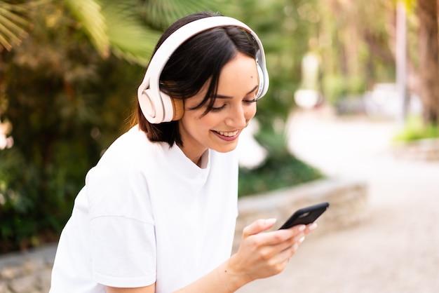 Mujer joven escuchando música al aire libre