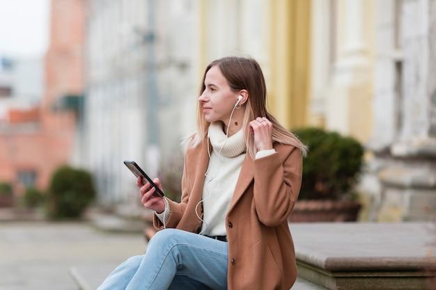 Mujer joven escuchando música en auriculares en la ciudad