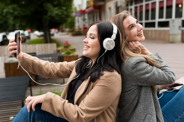 Mujer joven escuchando música en auriculares junto a su amiga