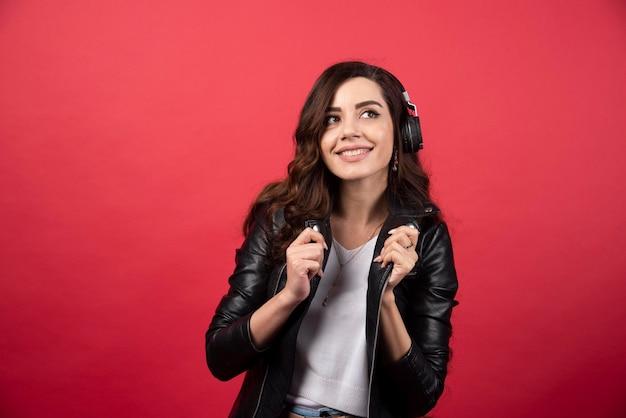 Mujer joven escuchando música en auriculares y posando sobre un fondo rojo. foto de alta calidad