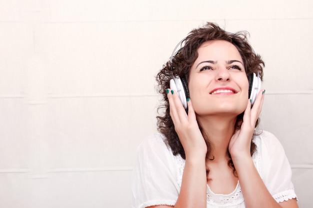Una mujer joven escuchando música con auriculares.