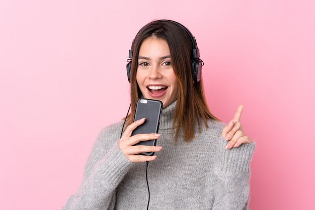 Mujer joven escuchando música y cantando con auriculares sobre pared rosa aislado