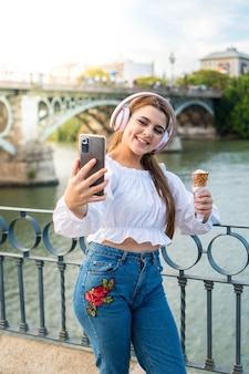 Mujer joven escuchando música comiendo un helado al aire libre en verano y tomando una foto