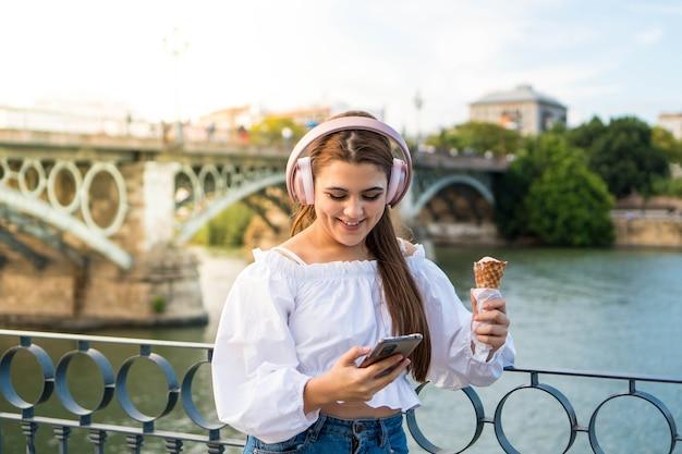 Mujer joven escuchando música y comiendo un helado al aire libre en verano