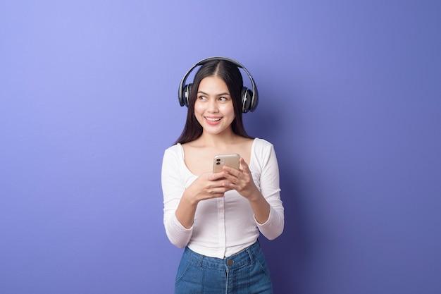 La mujer joven está escuchando música en fondo púrpura