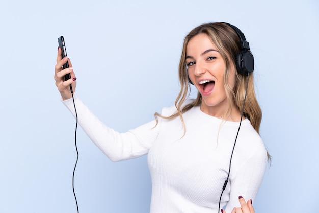 Mujer joven escuchando música y haciendo gesto de guitarra