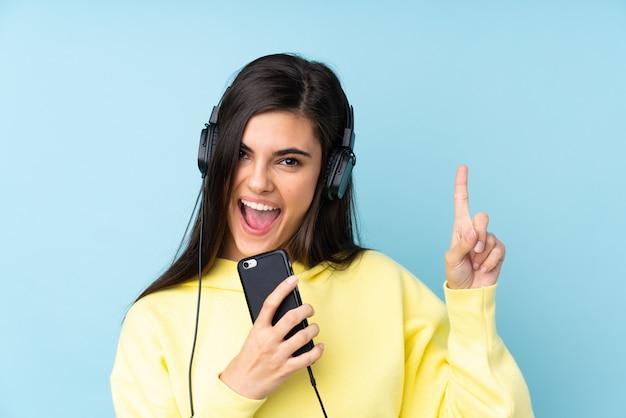 Mujer joven escuchando música con un móvil y cantando