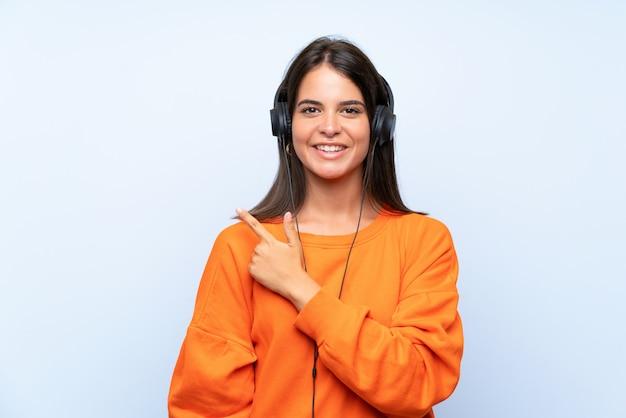 Mujer joven escuchando música con un móvil sobre pared azul aislado apuntando hacia un lado para presentar un producto