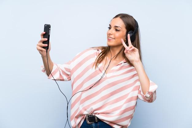 Mujer joven escuchando música con un móvil sobre pared azul aislado