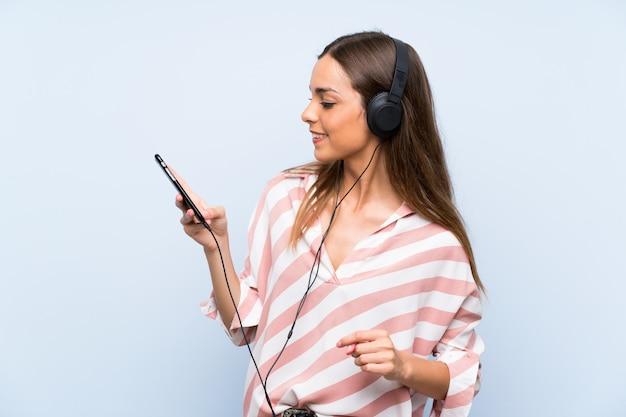 Mujer joven escuchando música con un móvil sobre pared azul