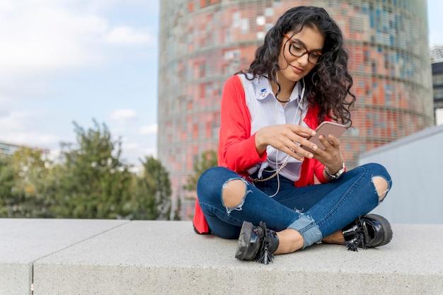 Una mujer joven escuchando música en tableta digital sentada
