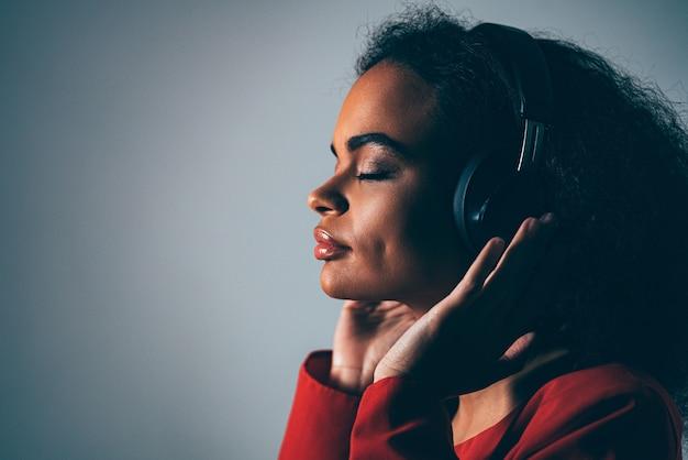 Mujer joven escuchando su pista favorita en auriculares con chaqueta roja top negro debajo aislado en la pared gris