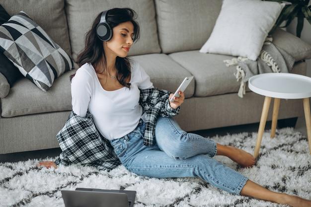 Mujer joven, escuchar música, en, auriculares