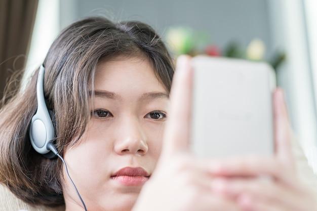 Mujer joven, escuchar música, de, teléfono móvil