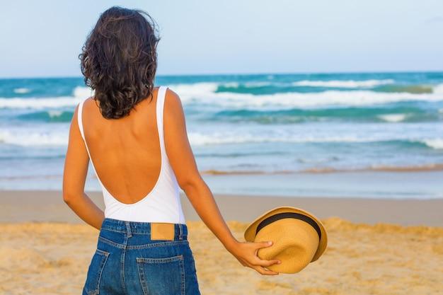 Mujer joven espalda con espalda en la playa
