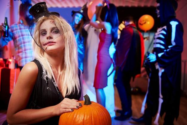 Mujer joven espeluznante con calabaza naranja