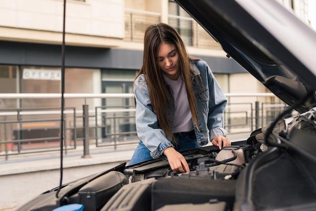 Mujer joven espera ayuda cerca de su coche averiado al lado de la carretera.