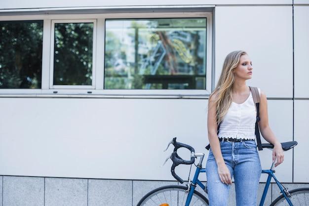Mujer joven esperando a alguien con bicicleta