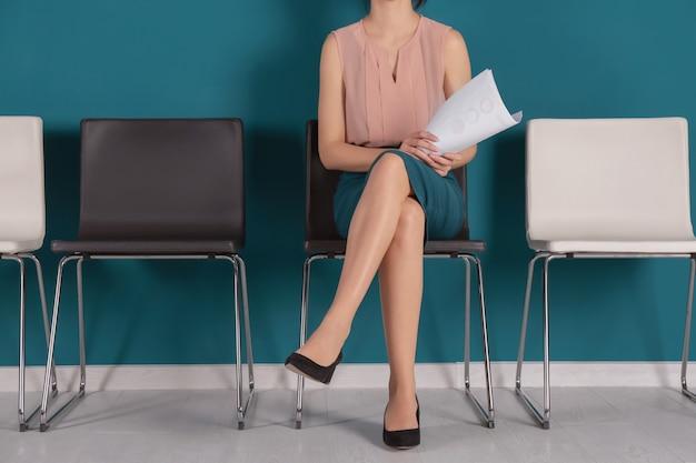 Mujer joven esperando una entrevista de trabajo en el interior