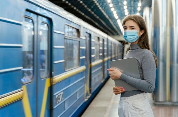 Mujer joven esperando en una estación de metro con una tableta