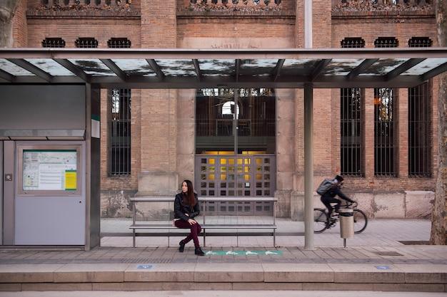 Mujer joven esperando en la parada del tranvía