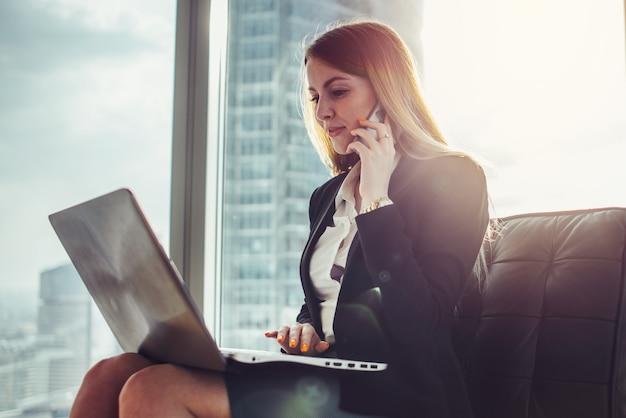 Mujer joven esperando en un pasillo sentado en la oficina moderna trabajando en equipo portátil hablando por teléfono.