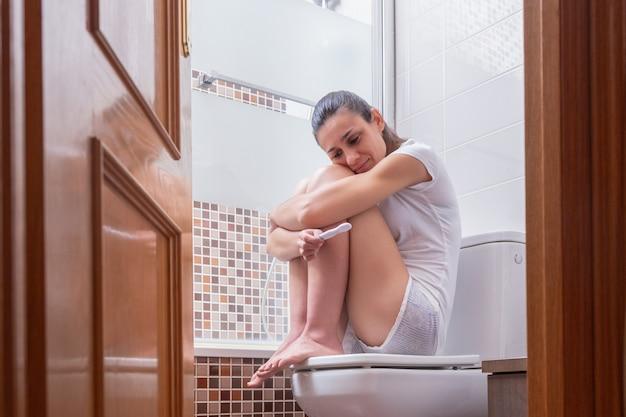 Mujer joven, esperando tranquilamente el resultado de la prueba de embarazo en el baño de su casa.