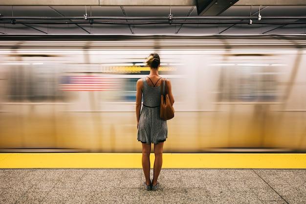 Mujer joven esperando el tren subterráneo en la ciudad de nueva york