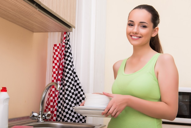 Mujer joven esposa lavando platos en la cocina