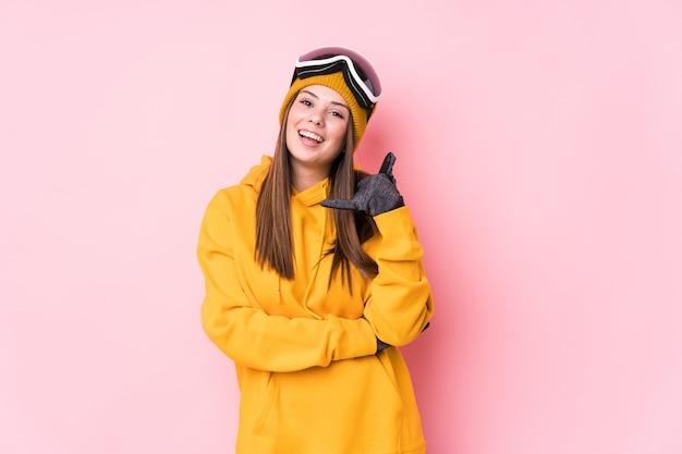 Mujer joven esquiador caucásico mostrando un gesto de llamada de teléfono móvil con los dedos.