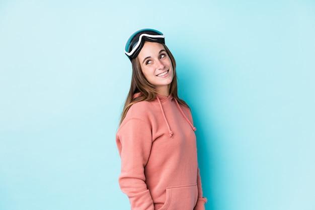 La mujer joven del esquiador mira a un lado sonriente, alegre y agradable.