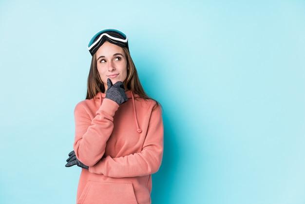 Mujer joven esquiador mirando hacia los lados con expresión dudosa y escéptica.
