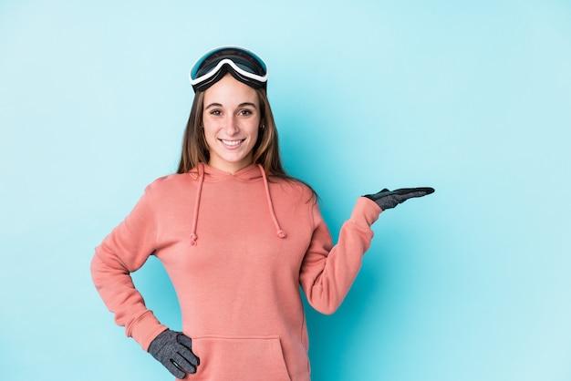 Mujer joven esquiador mostrando un espacio en blanco en una palma y sosteniendo otra mano en la cintura.