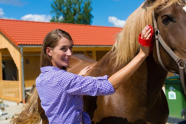 Mujer joven en el establo con caballo