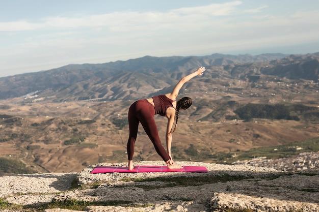 Mujer joven en estera calentando antes de practicar yoga