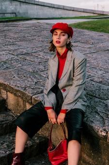 Una mujer joven con estilo atractiva que sostiene el bolso en su mano