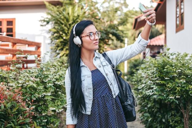 Mujer joven con estilo caminando con teléfono inteligente, escuchando música en auriculares, tomando fotos, estilo denim vintage, vacaciones de verano