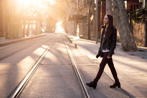 Mujer joven con estilo cruzando la calle al atardecer