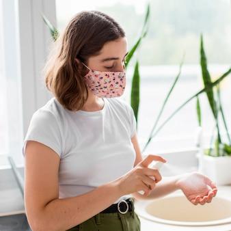 Mujer joven con estilo desinfectar las manos