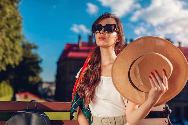 Mujer joven con estilo en gafas de sol con sombrero al aire libre. chica elegante saludando con sombrero descansando en un banco en un día caluroso en lviv