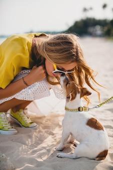 Mujer joven con estilo hipster sosteniendo caminar jugando perro cachorro jack russell, parque tropical, sonriendo y divirtiéndose, vacaciones, gafas de sol, gorra, camisa amarilla, arena de playa
