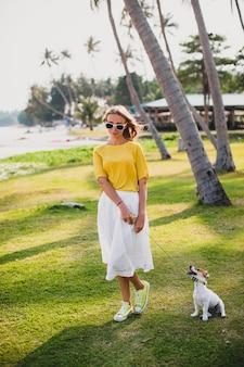 Mujer joven con estilo hipster sosteniendo caminar y jugar con perro en el baech