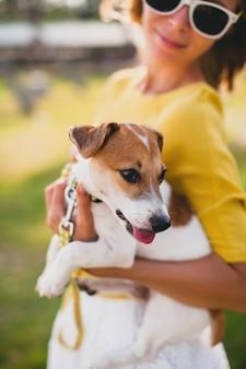 Mujer joven con estilo hipster sosteniendo caminar y jugar con perro