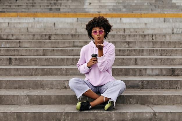 Mujer joven con estilo en jeans, sudadera con capucha rosa y gafas de sol coloridas sopla beso, sostiene la taza de café y se sienta en las escaleras al aire libre