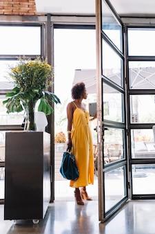 Mujer joven con estilo de pie cerca de la entrada del restaurante
