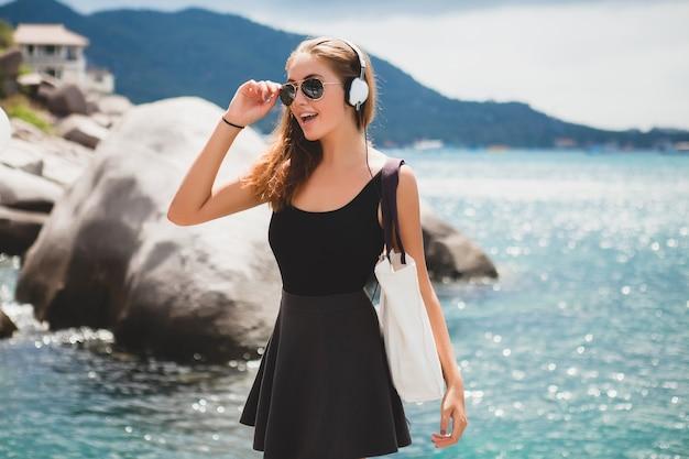 Mujer joven con estilo sexy hipster con una bolsa de compras durante las vacaciones, gafas de sol de aviador, auriculares, escuchando música, feliz, disfrutando del sol, paisaje de la laguna azul de la isla tropical